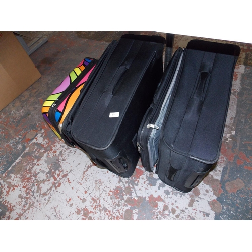 84 - THREE SUITCASES - TWO MATCHING BLACK AND ONE MULTI COLOURED...