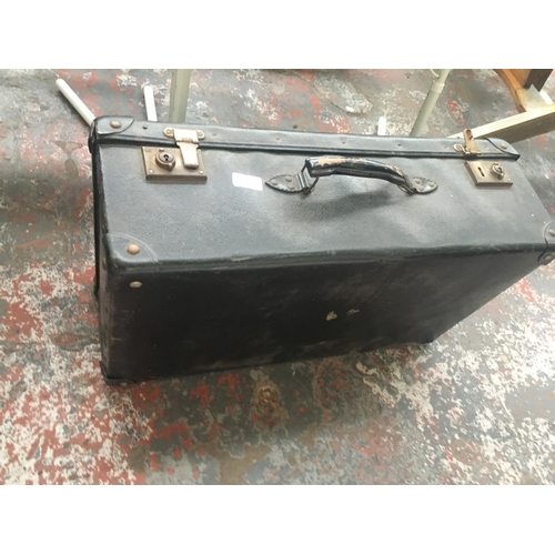 24 - THREE ITEMS TO INCLUDE A VINTAGE BLACK SUITCASE AND TWO PLASTIC FOLDING TABLES ON METAL SUPPORTS...