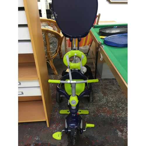 18 - THREE ITEMS TO INCLUDE A PURPLE AND GREEN CHILDS TRICYCLE, DESK FAN AND A CHOPPING BOARD...