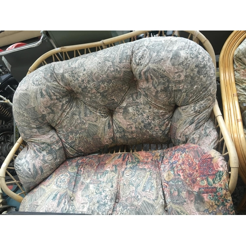 22 - A CANE TWO SEATER CONSERVATORY SETTEE WITH FLORAL UPHOLSTERY...