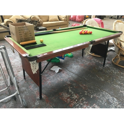 23A - A 6' X 3' WOODEN SNOOKER TABLE ON FOLDING METAL SUPPORTS WITH SNOOKER BALLS, RED AND YELLOW POOL BAL...