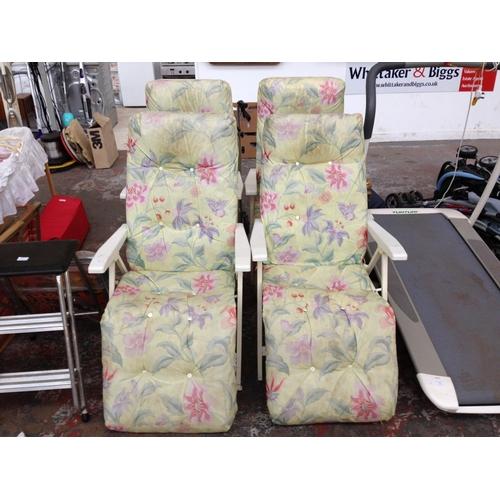 18 - FOUR METAL GARDEN SUN LOUNGERS WITH FLORAL UPHOLSTERY...