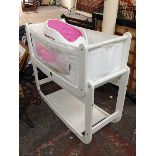 24 - A WHITE SNUZEPOD ROCKING CHILDS CRIB CONTAINING FISHER PRICE PIGGY BANK, ANGEL CARE BABY CHANGING ST...