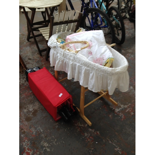 35 - TWO ITEMS TO INCLUDE WICKER MOSES BASKET ON WOODEN ROCKING SUPPORT STAND AND A RED TRAVEL COT...