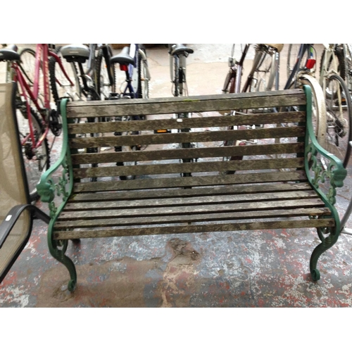 38 - A WOODEN SLATTED TWO SEATER GARDEN BENCH WITH CAST IRON ORNATE ENDS TOGETHER WITH A GOOD QUALITY FOL...