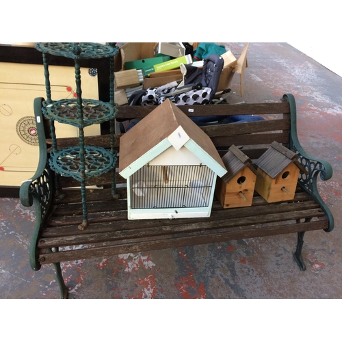 26 - FIVE ITEMS TO INCLUDE A CAST IRON ORNATE WOODEN SLATTED GARDEN BENCH, TWO BIRD BOXES, CANARY CAGE AN...