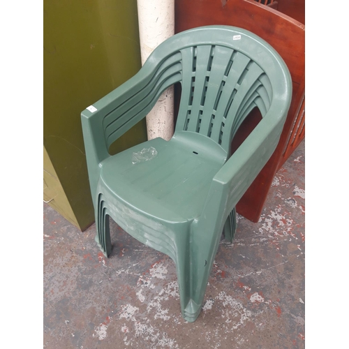 35 - FOUR GREEN PLASTIC STACKABLE GARDEN CHAIRS...