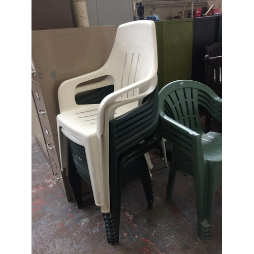 33 - TEN PLASTIC STACKABLE GARDEN CHAIRS, EIGHT GREEN AND TWO WHITE...