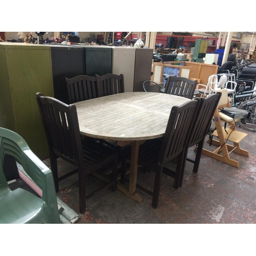 37 - A GOOD QUALITY TEAK OVAL PATIO TABLE WITH SIX DARK WOOD CHAIRS...