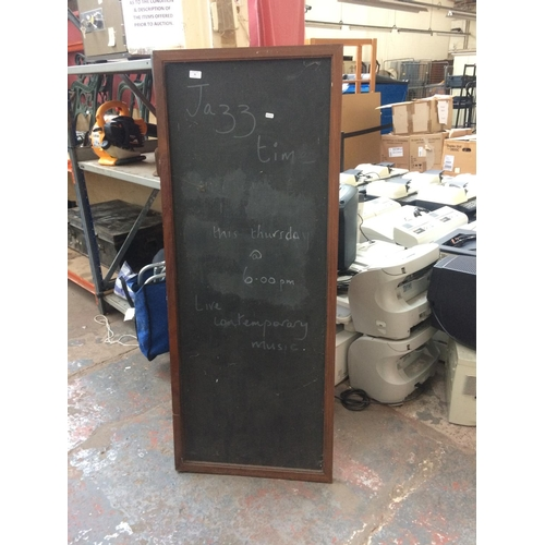 46 - A WOODEN FRAMED BLACKBOARD MEASURING APPROX 150cm x 60cm...