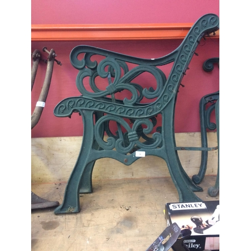 54 - A PAIR OF GREEN PAINTED CAST IRON ORNATE GARDEN BENCH ENDS...