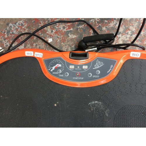 21 - AN ORANGE AND BLACK BTM VIBRATING EXERCISE MACHINE WITH LEAD (W/O)...
