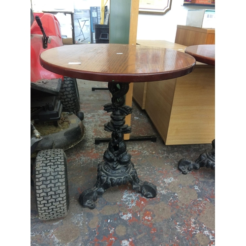 22 - A CIRCULAR WOODEN TOPPED PUB TABLE ON HEAVY CAST IRON ORNATE PEDESTAL BASE...