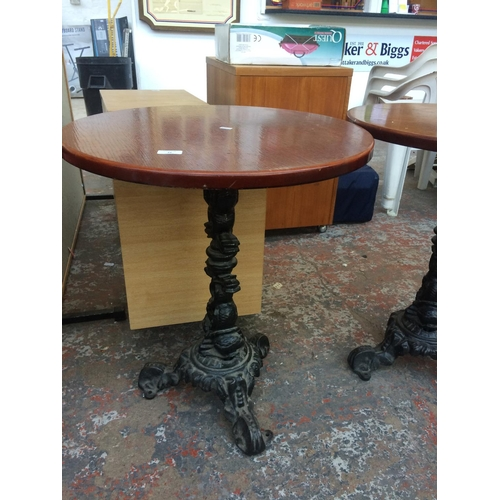 23 - A CIRCULAR WOODEN TOPPED PUB TABLE ON HEAVY CAST IRON ORNATE PEDESTAL BASE...