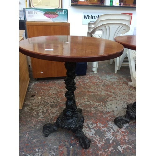 24 - A CIRCULAR WOODEN TOPPED PUB TABLE ON HEAVY CAST IRON ORNATE PEDESTAL BASE...