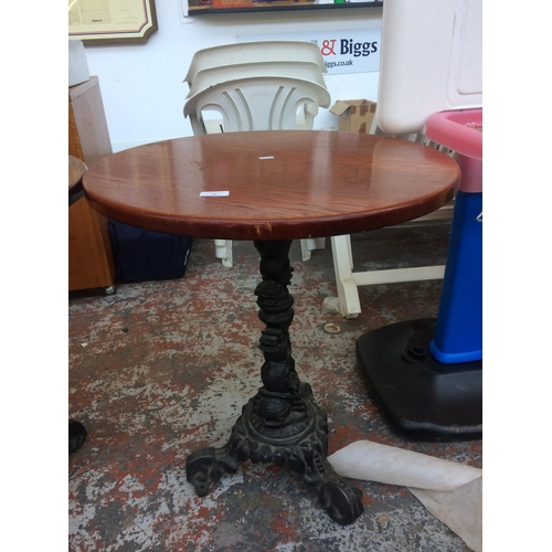 25 - A CIRCULAR WOODEN TOPPED PUB TABLE ON HEAVY CAST IRON ORNATE PEDESTAL BASE...