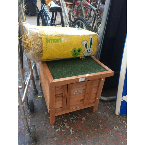 42 - A NEW WOODEN BUNNY BUSINESS RABBIT HUTCH WITH FELTED ROOF TOGETHER WITH A BAG OF STRAW...