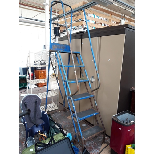 15 - A BLUE METAL WAREHOUSE FOUR WHEELED STAIRCASE...