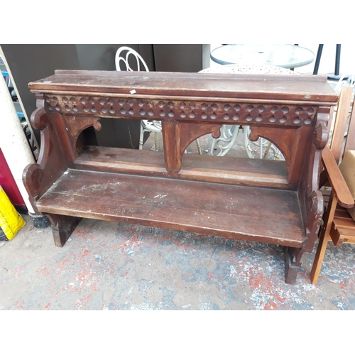 17 - A WOODEN CARVED CHURCH STYLE PEW...