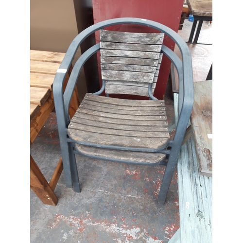 21 - TWO BLACK METAL STACKABLE GARDEN CHAIRS WITH WOODEN SLATS...