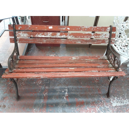 31 - A CAST IRON ORNATE GARDEN BENCH WITH WOODEN SLATS...