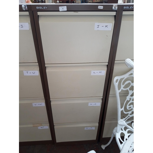 33 - A BROWN AND CREAM BISLEY FOUR DRAWER METAL OFFICE FILING CABINET WITH KEY...