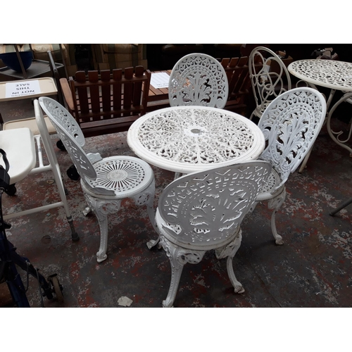 38 - A FIVE PIECE WHITE PAINTED CAST ALUMINIUM PATIO SET COMPRISING OF A CIRCULAR TABLE AND FOUR MATCHING...