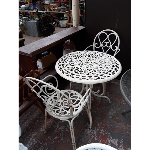 39 - A THREE PIECE ORNATE METAL PATIO SET COMPRISING OF A CIRCULAR TABLE AND TWO MATCHING ARM CHAIRS...