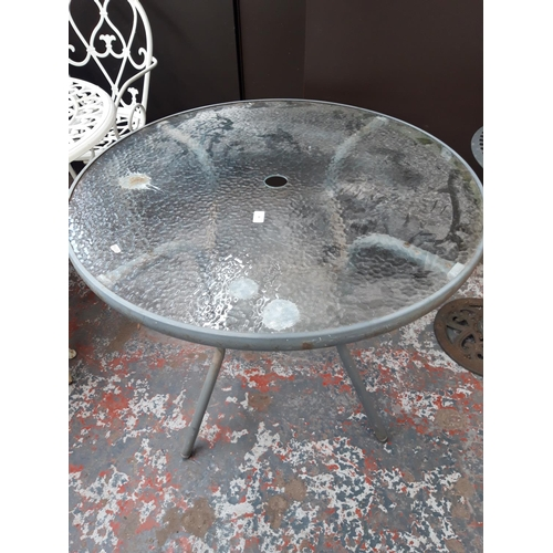 40 - A GREY METAL CIRCULAR GLASS TOPPED PATIO TABLE...