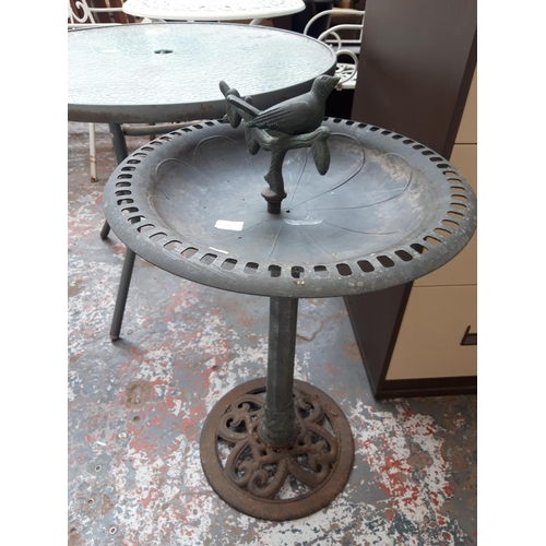 41 - A PLASTIC PEDESTAL BIRD BATH ON CAST IRON BASE...