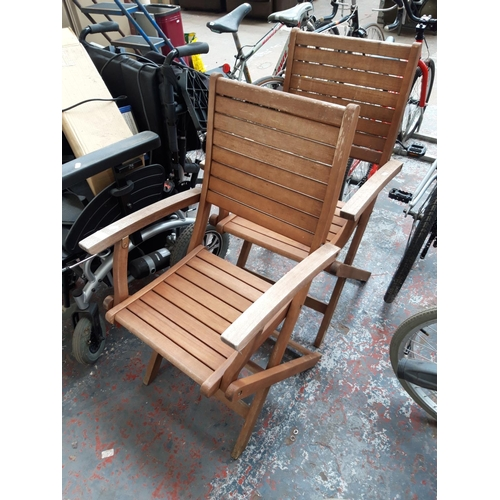 47 - A PAIR OF MATCHING TEAK FOLDING PATIO ARMCHAIRS...