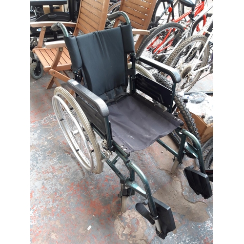 48 - A BLACK AND GREEN WORLD WIDE MOBILITY FOLDING WHEELCHAIR...