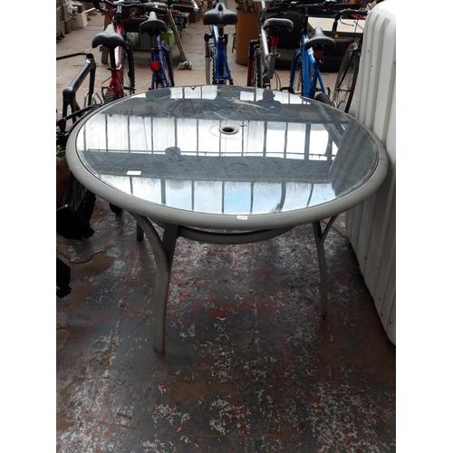 49 - A GREY METAL CIRCULAR GLASS TOPPED PATIO TABLE...