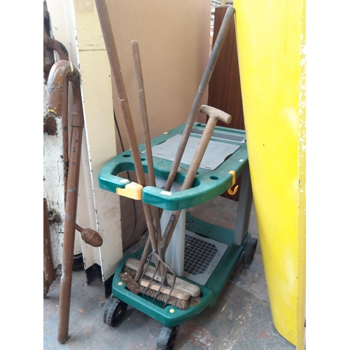 54 - A GREEN PLASTIC GREENHOUSE WORKSTATION CONTAINING GARDEN FORK, HOE, BRUSHES ETC....