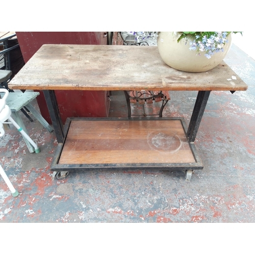 29 - A HEAVY DUTY METAL FOUR WHEELED WORKSHOP TABLE WITH WOODEN TOP AND LOWER SHELF...