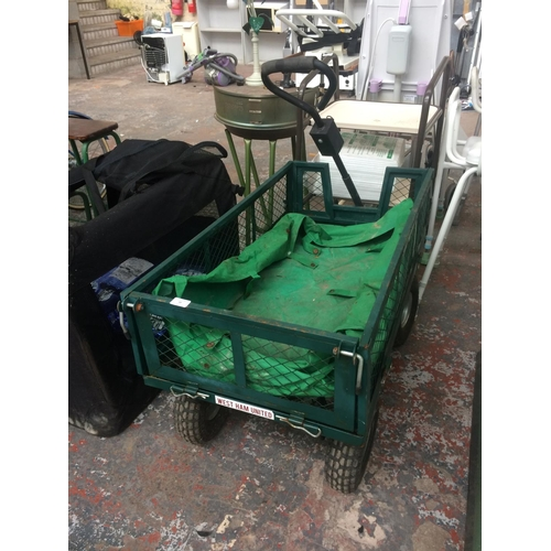 10 - A GREEN MESHED METAL FOUR WHEELED WAREHOUSE TRUCK WITH STEERING...