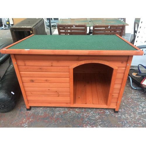 13 - AN AS NEW WOODEN DOG KENNEL WITH GREEN FELTED ROOF MEASURING 115.7 CM X 78.5 CM X 81.3 CM...