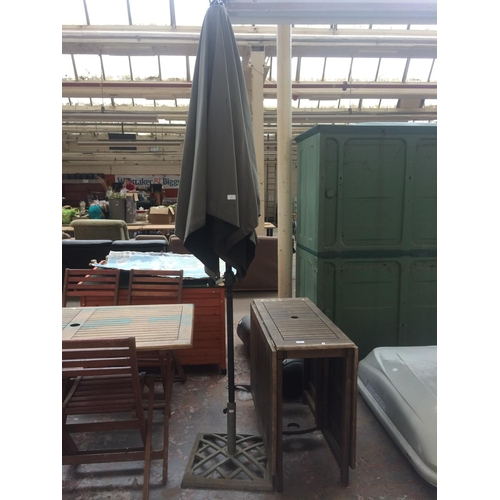 23 - TWO ITEMS TO INCLUDE A GARDEN PARASOL WITH CAST IRON BASE TOGETHER WITH A WOODEN DROP LEAF PATIO TAB...