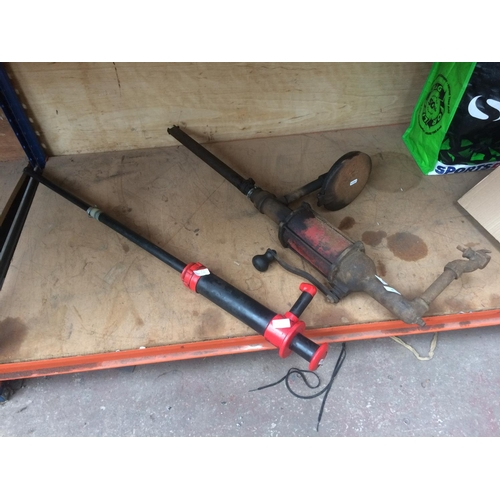 40 - A 1940's VINTAGE CAST IRON OIL PUMP AND A BLACK AND RED PLASTIC OIL PUMP (W/O)...