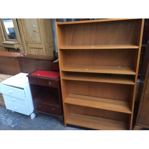 451 - THREE ITEMS TO INCLUDE A BEECH EFFECT BOOKCASE WITH FIVE SHELVES, MAHOGANY EFFECT CABINET WITH RED L...