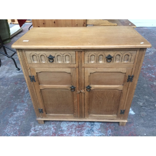 479 - AN OAK SIDEBOARD WITH TWO DOORS AND TWO DRAWERS...