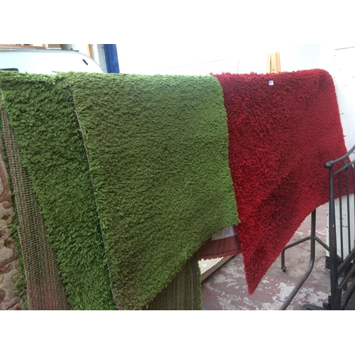 483 - A LARGE RED RUG AND TWO GREEN RUGS...