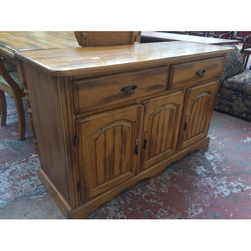 514 - A GOOD QUALITY HEAVY OAK DINING TABLE WITH SIX MATCHING CHAIRS AND MATCHING SIDEBOARD WITH THREE DOO...