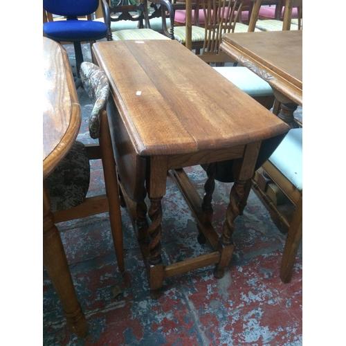 518 - AN OAK DROP LEAF DINING TABLE ON BARLEY TWIST SUPPORTS...