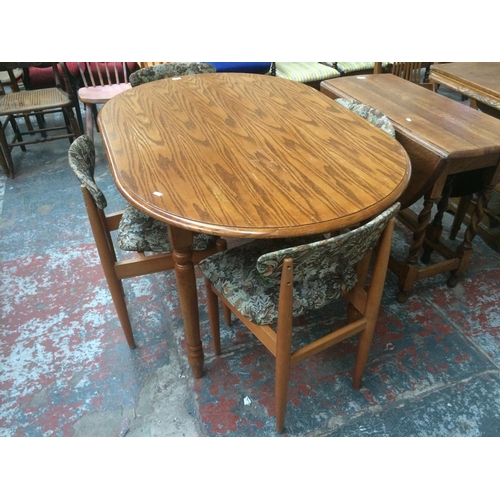 519 - A TIGER OAK DINING TABLE AND FOUR VINTAGE TEAK DINING CHAIRS...
