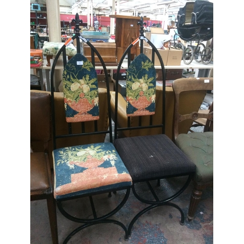 523 - TWO BLACK CAST IRON DINING CHAIRS...