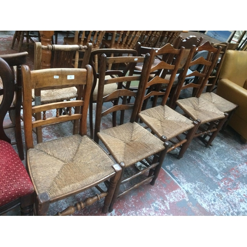 536 - FIVE VARIOUS OAK FRAMED CHESHIRE LADDER BACK CHAIRS WITH RUSH SEATS TO INCLUDE ONE ROCKING CHAIR...