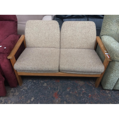 541 - A VINTAGE OAK FRAMED BEIGE UPHOLSTERED TWO SEATER SOFA...