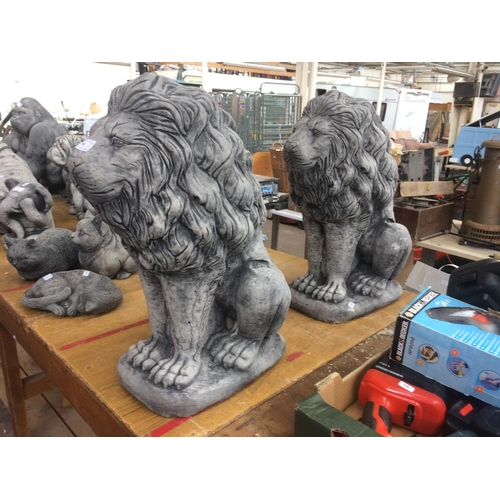85 - A PAIR OF GOOD QUALITY RECONSTITUTED STONE MALE LION GARDEN ORNAMENTS...