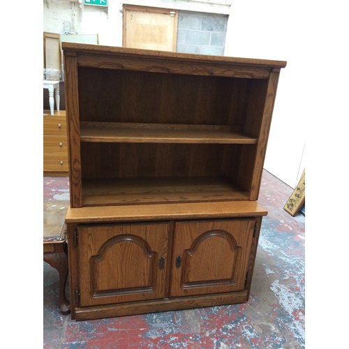 466 - AN OAK EFFECT BOOKCASE WITH TWO LOWER DOORS AND TWO SHELVES...